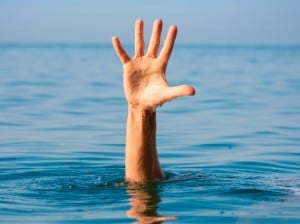 The single hand of a drowning man illustrates how it feels to be out of organizational alignment, as seen by leadership speakers Bob Vanourek & Gregg Vanourek.