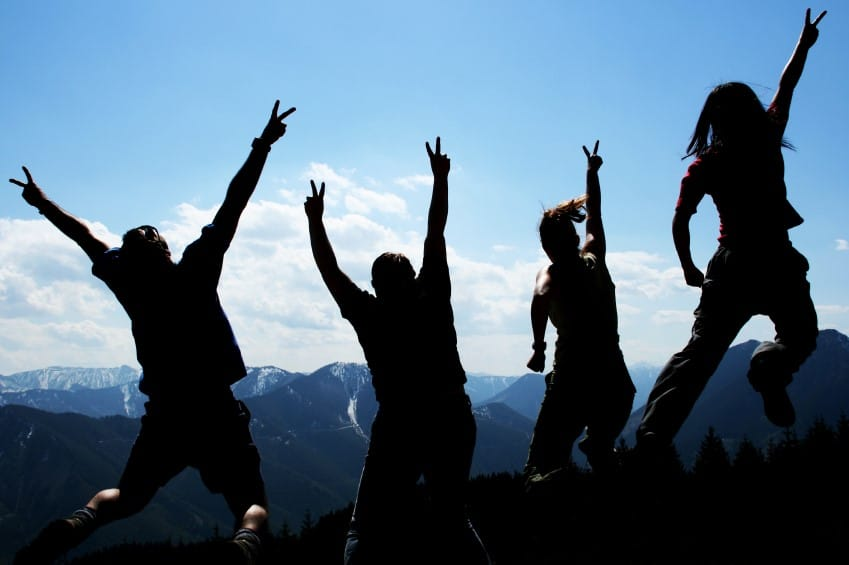 Leadership Speakers and Authors, Bob and Greg Vanourek, use an image of triumphant hikers on a mountain top to illustrate the importance of team work in leadership.