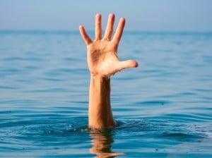 The single hand of a drowning man illustrates how it feels to be out of organizational alignment, as seen by leadership speakers Bob Vanourek & Gregg Vanourek.