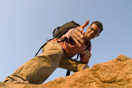 Leadership speaker and author Bob Vanourek uses this image of a man on top of a rock ledge reaching out to help the next person up to illustrate the importance of trust in the workplace.