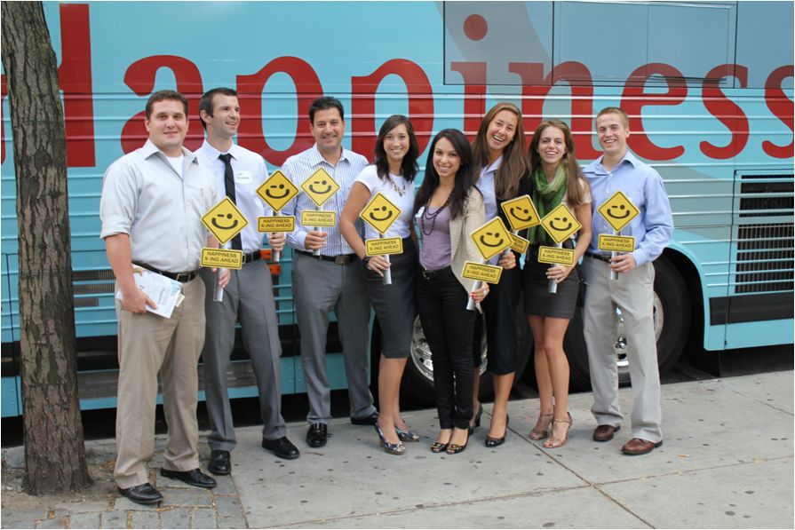 """Zappos employees in front of their """"Delivering Happiness"""" bus"""